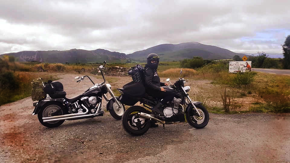 Motobabe Linda Delaney from Morrigan Womens Motorcycle Club sitting on her suzuki Bandit next to Harley Davidson Fatboy sharing what to pack for motorcycle camping tips