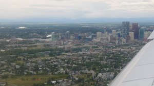 Blue mountains in background, tall buildings of downtown Calgary in middle, green space with low buildings in front