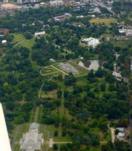 green park seen from the air, mainly trees but the iconic Palm House of Kew Gardens is recognizable