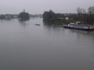 broad, flat river on a grey day, one rowing team coming toward the boat at Kew Pier