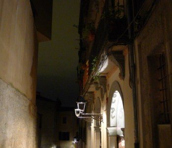 Dark narrow alley lit by lights from inside open door, all in romantic stone