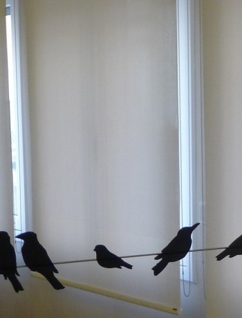 Silhouettes of black birds on a wire, shown on a mirror on a hotel room wall