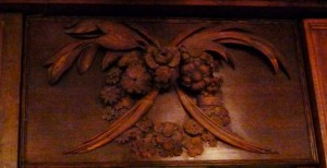 Richly detailed three-dimensional dark wood carving of a wreath of flowers and leaves