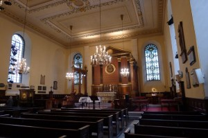 Interior of a classic church with warm light from chandelier, white ceiling with gold decoration, dark brown pews
