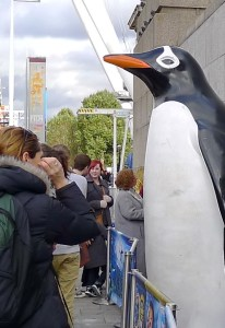 A statue of a penguin towers over tourists