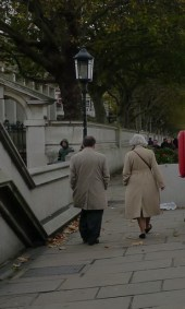 A man and woman walk away from the camera, the woman in front, she has white hair