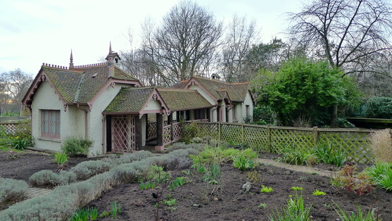 Quaint English cottage with a garden in front, much bare ground and a few plants