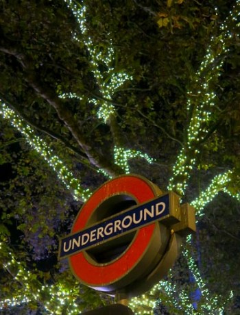 A London Underground sign with Christmas lights at night