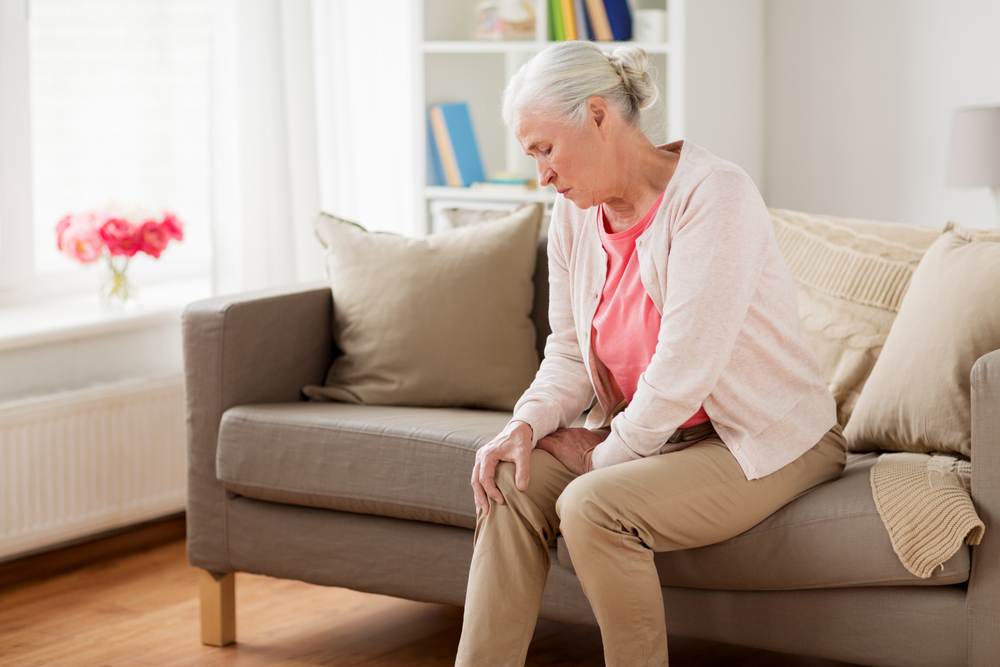 A woman with arthritis grabs her knee in pain. Physical therapy can help arthritis pain relief.