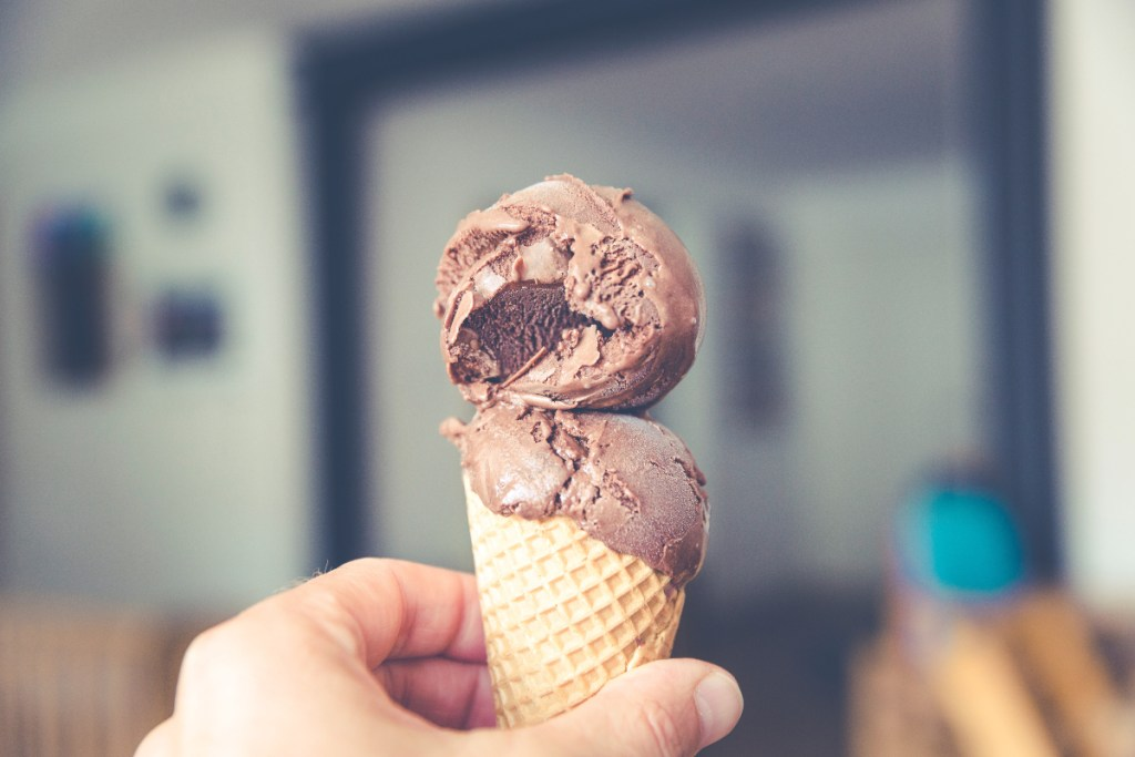 Image of a hand holding an ice cream cone. Dairy is one of many foods that cause inflammation.