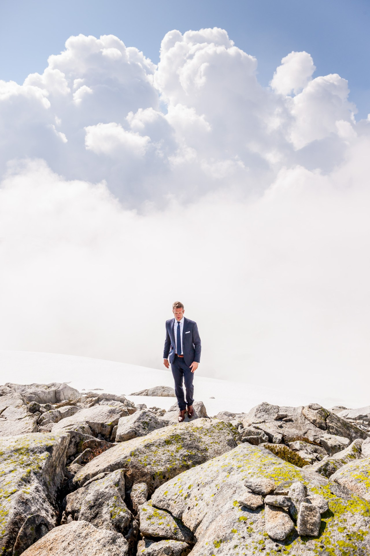 Jay Demerit in suit at top of mountain in Vancouver BC.