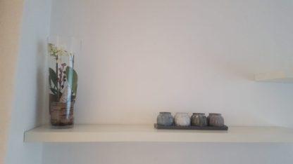 wit plankjes met grijze kaarsjes en plant