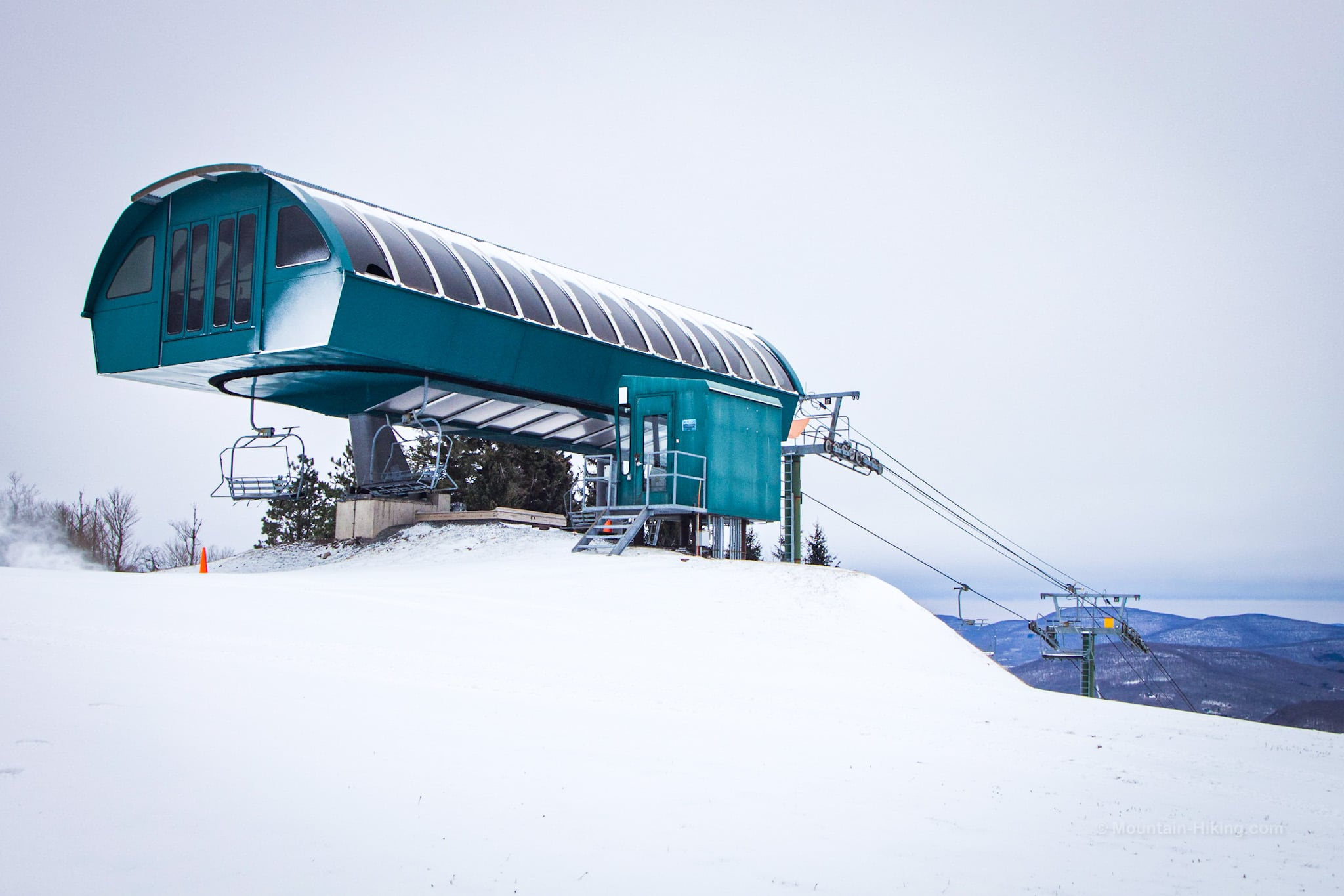 green ski lift building in snow