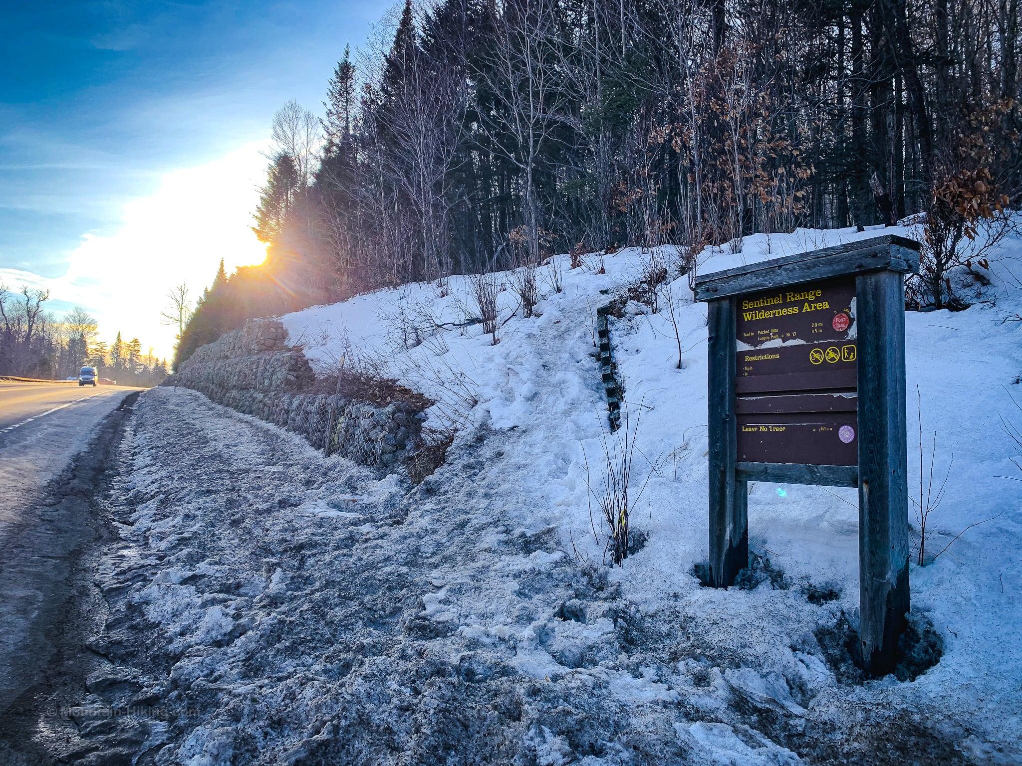 Trailhead sign beside road