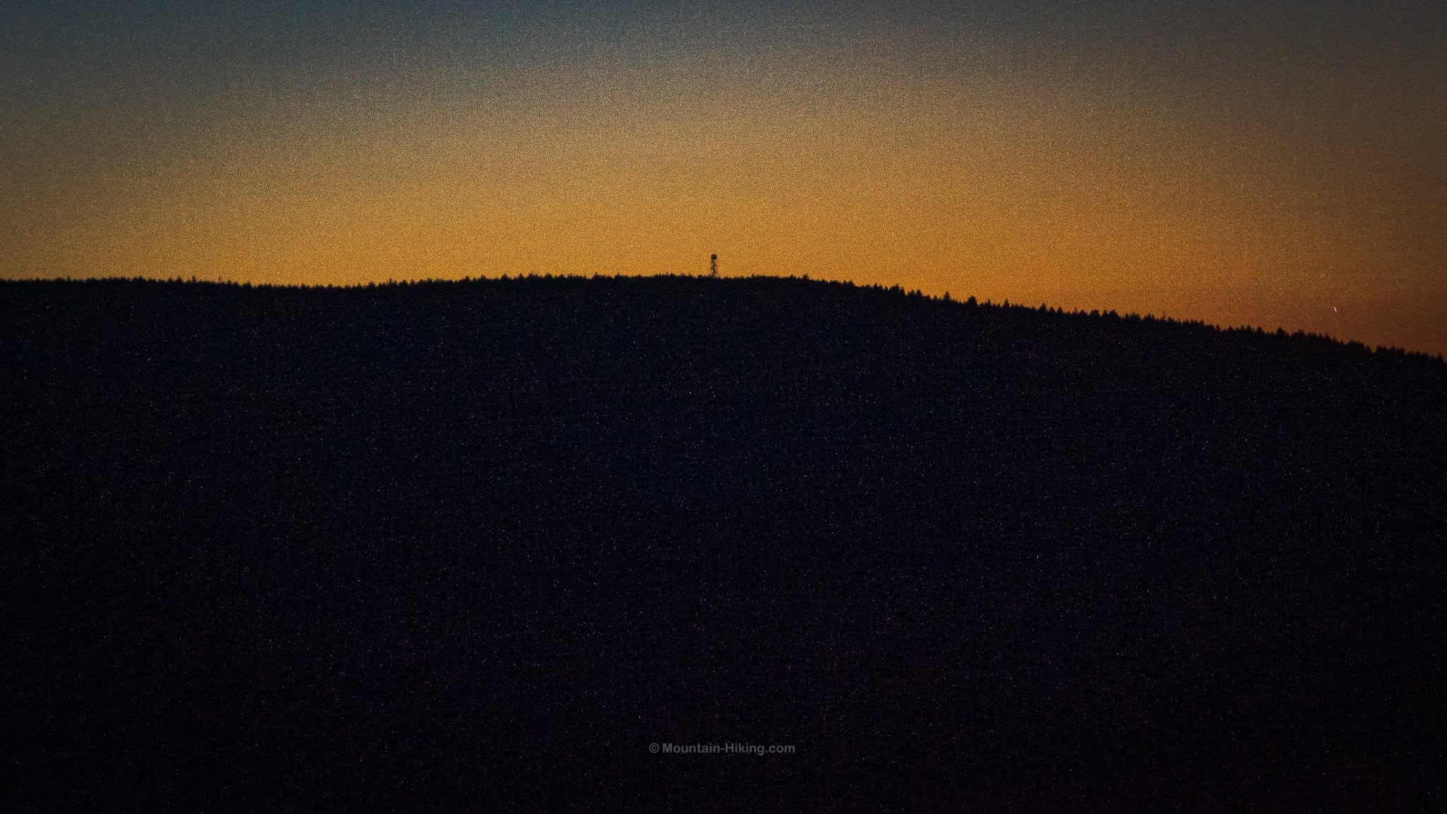 silhouette of fire tower on summit at dusk