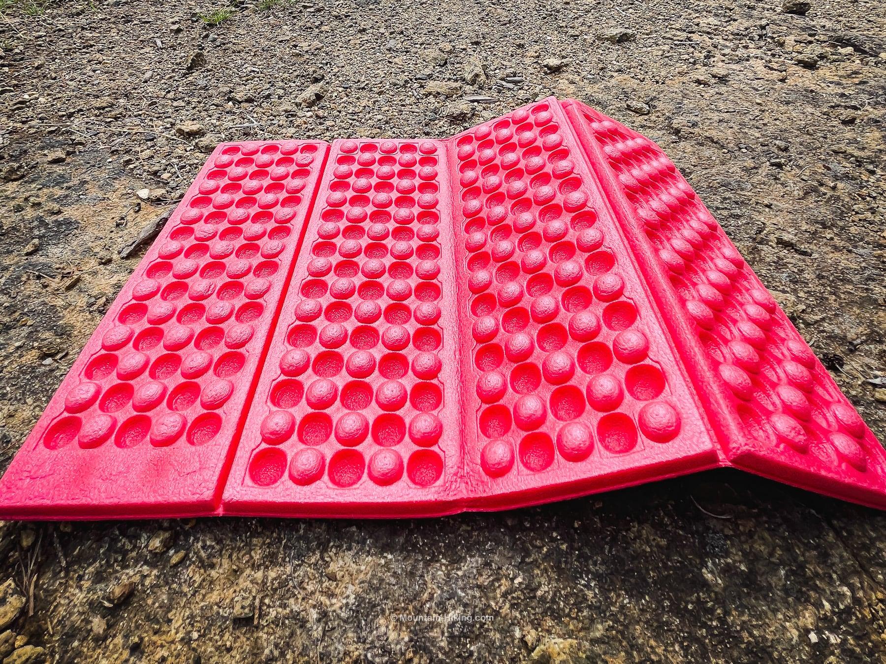 pink sit pad on lumpy rock