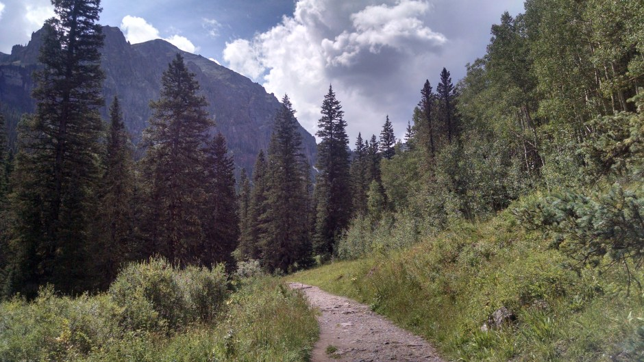 Headed towards Bear Creek Falls surround by pine trees and dramatic sheer vertical mountains