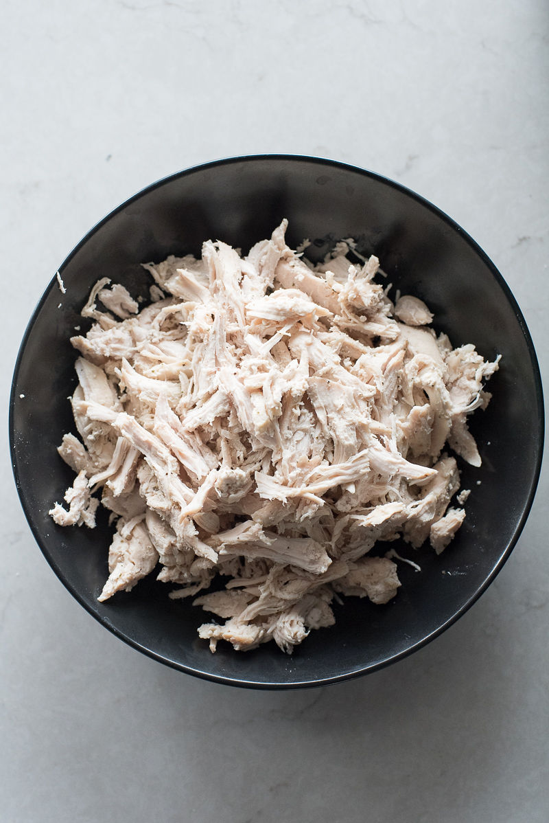 A slow cooker filled with a basic shredded chicken. This is a super versatile recipe. www.mountainmamacooks.com