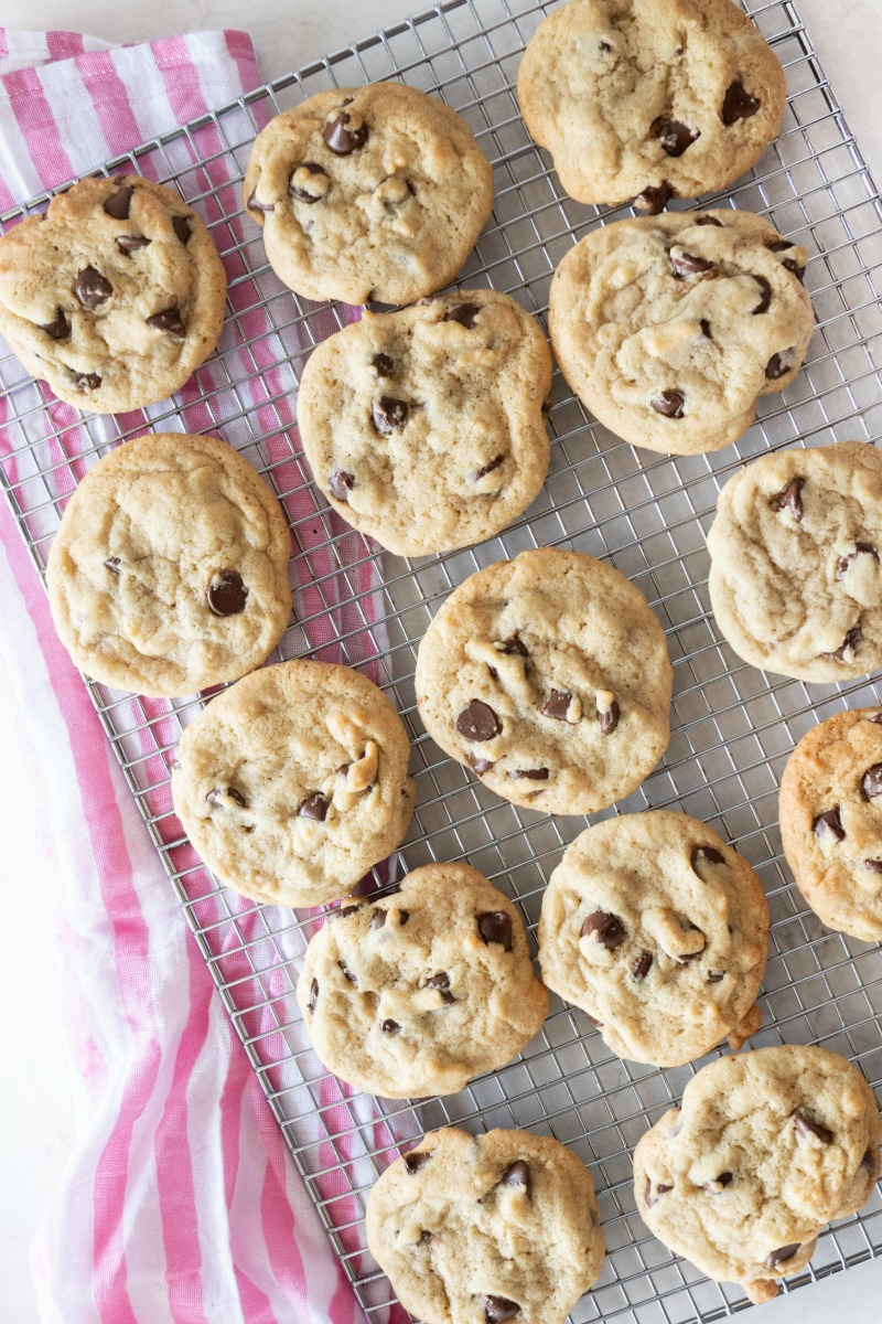 A cooling rack filled with a dozen perfect chocolate chip cookies ready to be eaten!