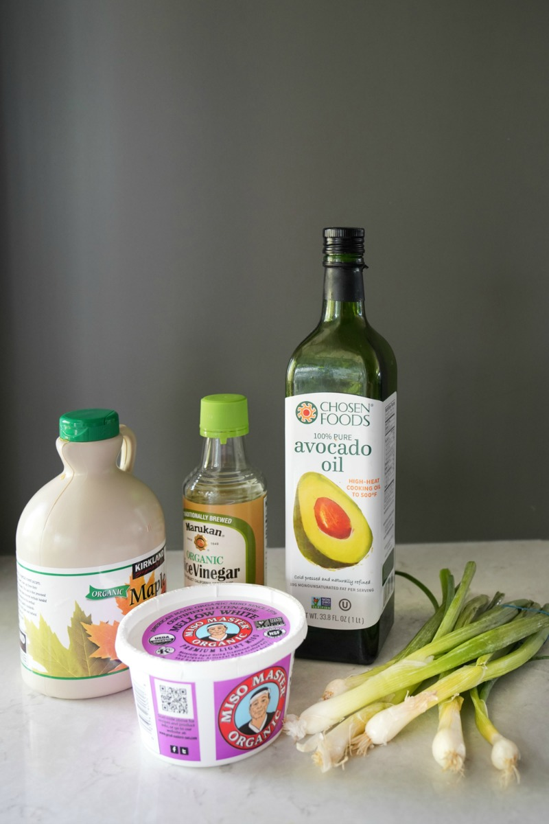 All the ingredients for making a miso dressing in the blender- avocado oil, miso, syrup, rice vinegar, and green onions
