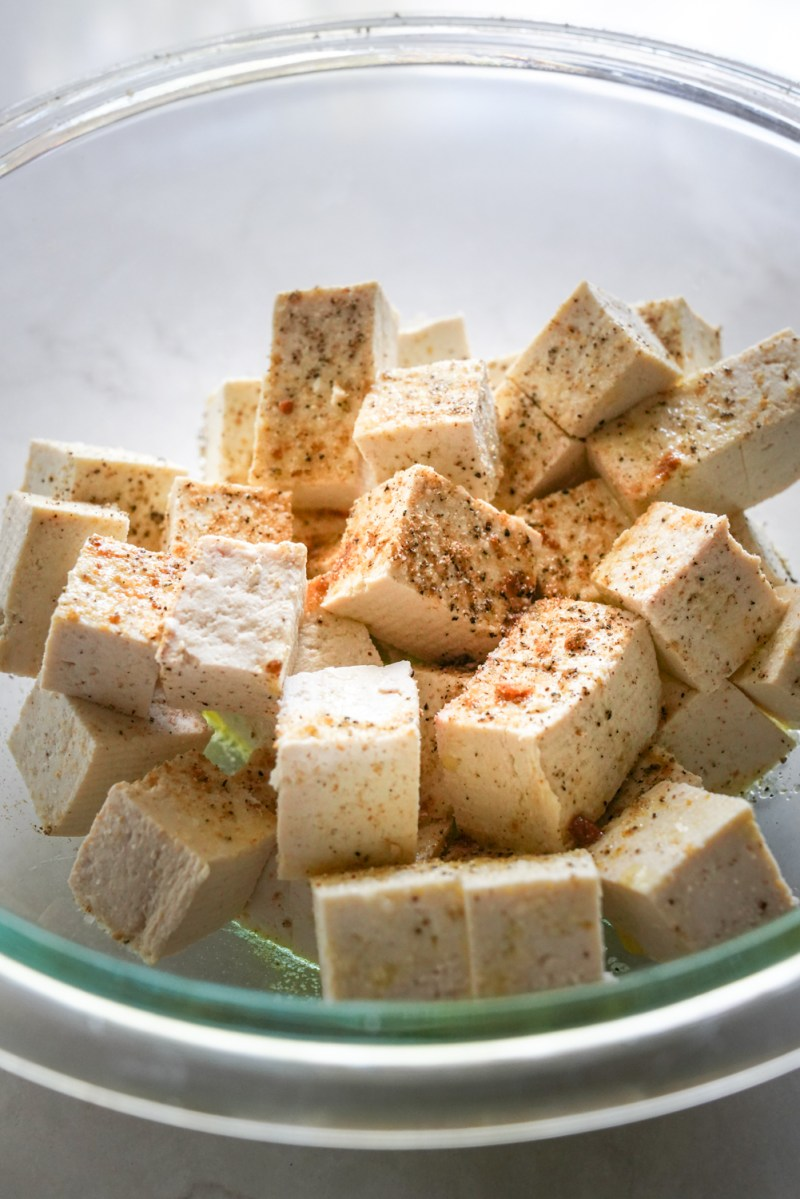 A bowl of cubed tofu that is seasoned with olive oil, garlic, cayenne, and onion. Ready for the oven!