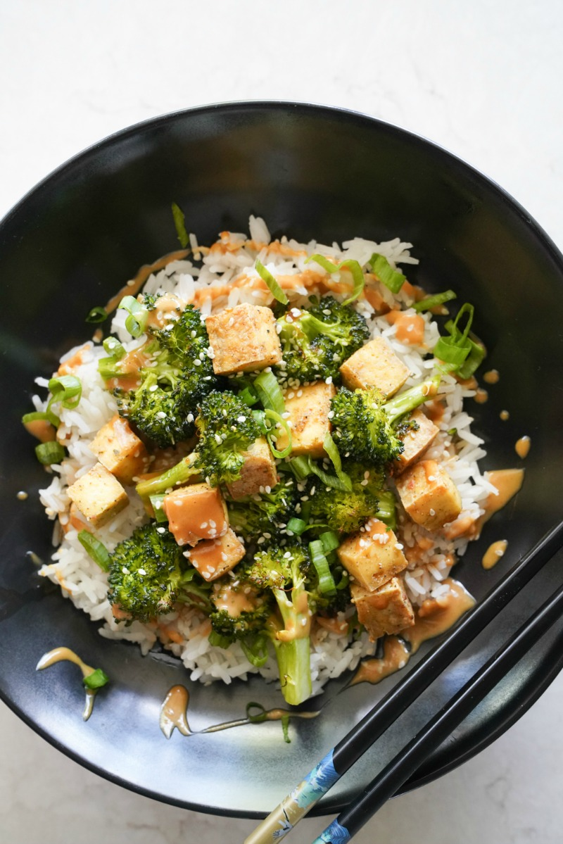 A beautiful black bowl filled with steamed rice and broccoli and tofu stir fry with a savory peanut sauce.