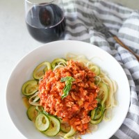 A plate of pasta and zucchini noodles with slow cooked turkey bolognese sauce and a glass of red wine.