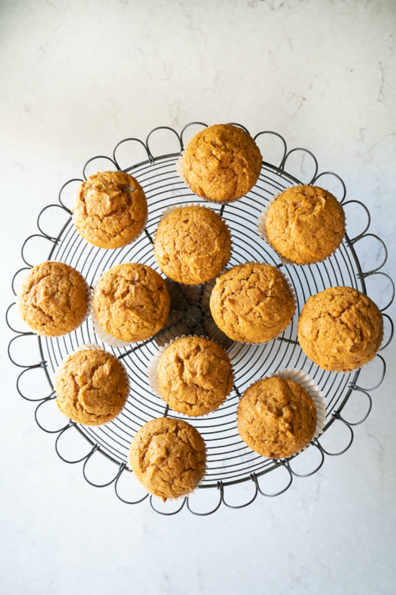 A wire tray on top of a white counter filled with pumpkin muffins. www.mountainmamacooks.com