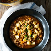 Wooden backdrop, black bowl, moody feel. A simple bowl of veggie lentil soup. www.mountainmamacooks.com