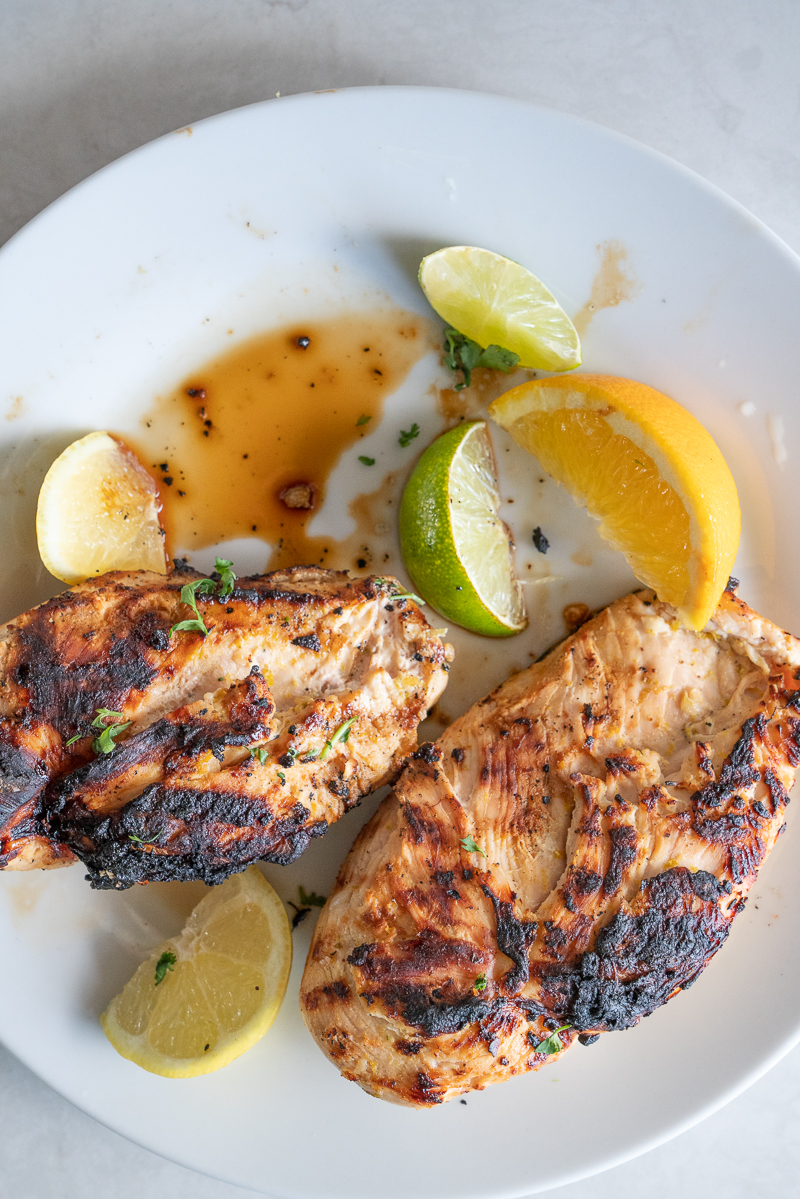 Two grilled garlic citrus chicken breasts with the juices on the plates and slices of citrus segments. www.mountainmamacooks.com