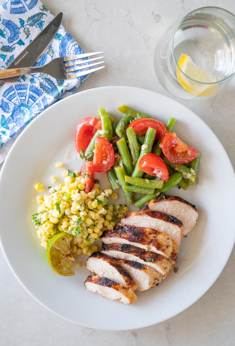 A plate with garlic citrus chicken, tomato and green bean salad, and a simple corn sauté. www.mountainmamacooks.com