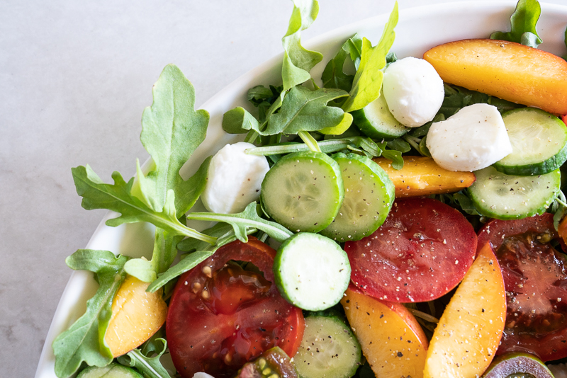 Summer arugula salad with peaches and mozzarella! A summertime caprese salad with a delicious basil-balsamic vinaigrette. www.mountainmamacooks.com