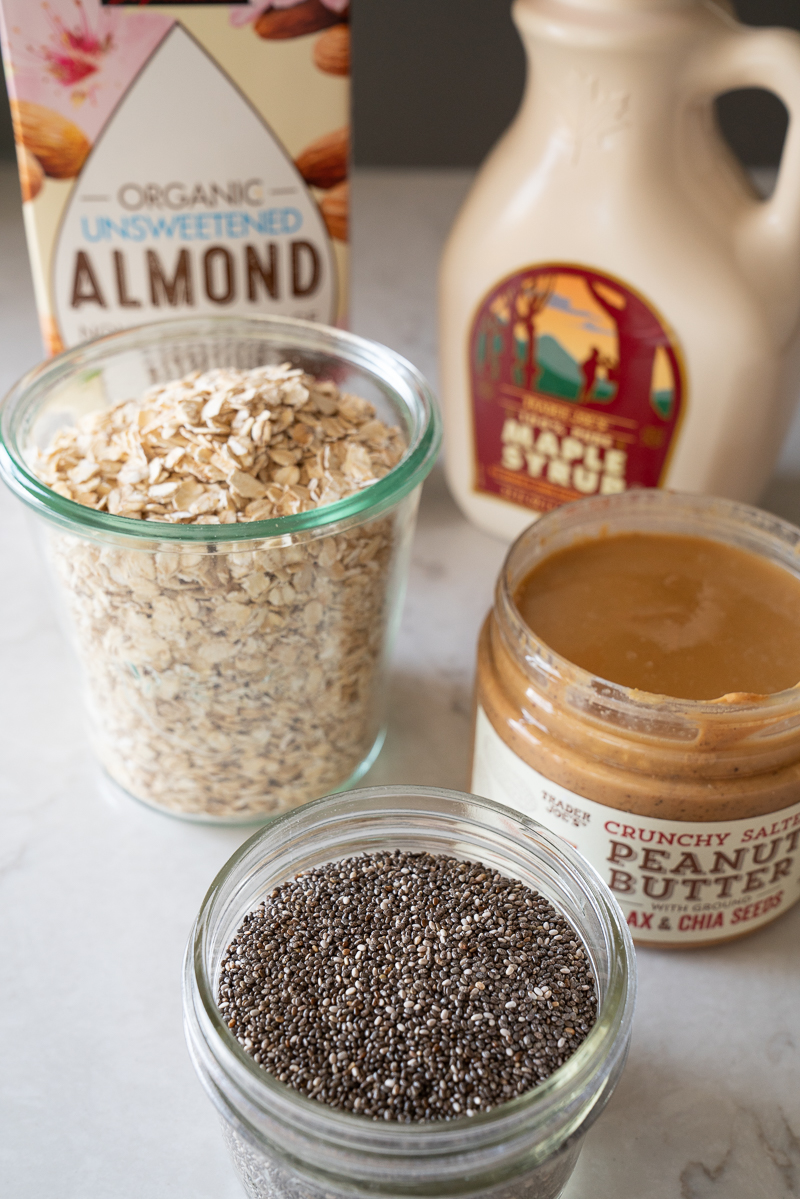 All the ingredients for making overnight oats: gluten free oats, almond milk, maple syrup, peanut butter, chia seeds. www.mountainmamacooks.com