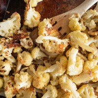 A sheet pan full of roasted cauliflower with parmesan cheese. A small plate full of golden crusted cauliflower florets. Simply delicious recipe! www.mountainmamacooks.com