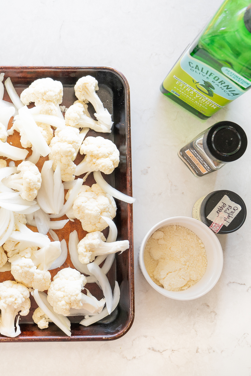 Ingredients for a simply roasted cauliflower- florets, olive oil, garlic powder, salt, pepper, crushed red pepper, and parmesan cheese. www.mountainmamacooks.com