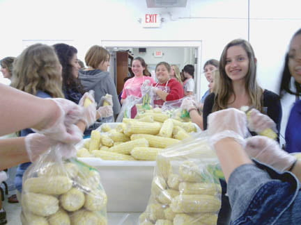 Members of the Greenbrier East FFA help fellow members process their corn to sale through the Farm to School program.