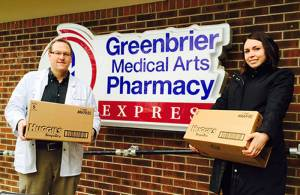 Rick Leatherman, R.Ph., managing pharmacist for Greenbrier Medical Arts Pharmacy in Fairlea, presents boxes of toiletries, baby supplies and over-the-counter medications to Rachael Austin, prevention educator with FRC.