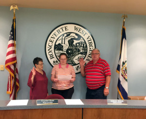 Council members Gail White (left) and Robert Baker are sworn in during Monday's meeting of the Ronceverte City Council by recorder Crystal Byer. White is a former mayor of the city, and Baker was reelected to his post.