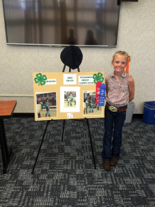 "Josi Ervin with her poster from her State 4-H Days Visual Presentation ""Ewe First."""