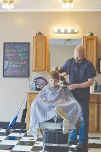 Witness the classic barbershop image - Jeremy Hill is giving Kaden Hall, 6 years of age, a trim as he sits in the big barber's chair at Jeremy's Barbershop on Court Street North. Photo by Peggy Mackenzie