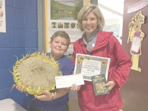 Lewisburg House and Garden Club President Townley Hamilton congratulates John Wade, fourth grader in Ms. Holden's Room, on his achievement as Grand Winner in the Sunflower Contest on  Friday, Sept. 30, at Lewisburg Elementary School. His sunflower measured 46-1/2 inches, and he was presented with a $25 check, a certificate and a Birds of West Virginia book.