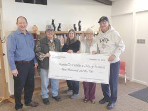 Appalachian Power External Affairs Manager Ronn Robinson presents a $2,000 donation from the company's volunteer readers to Rainelle Library Board members as part of Read to Me Day. Employees made a contribution to libraries in four flood damaged counties.