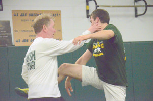 While giving basic instructions to a crowd of wrestlers, head coach Brian Miluk uses senior wrestler Logan Evans to demonstrate what he's teaching. (Mark Robinson Photo)