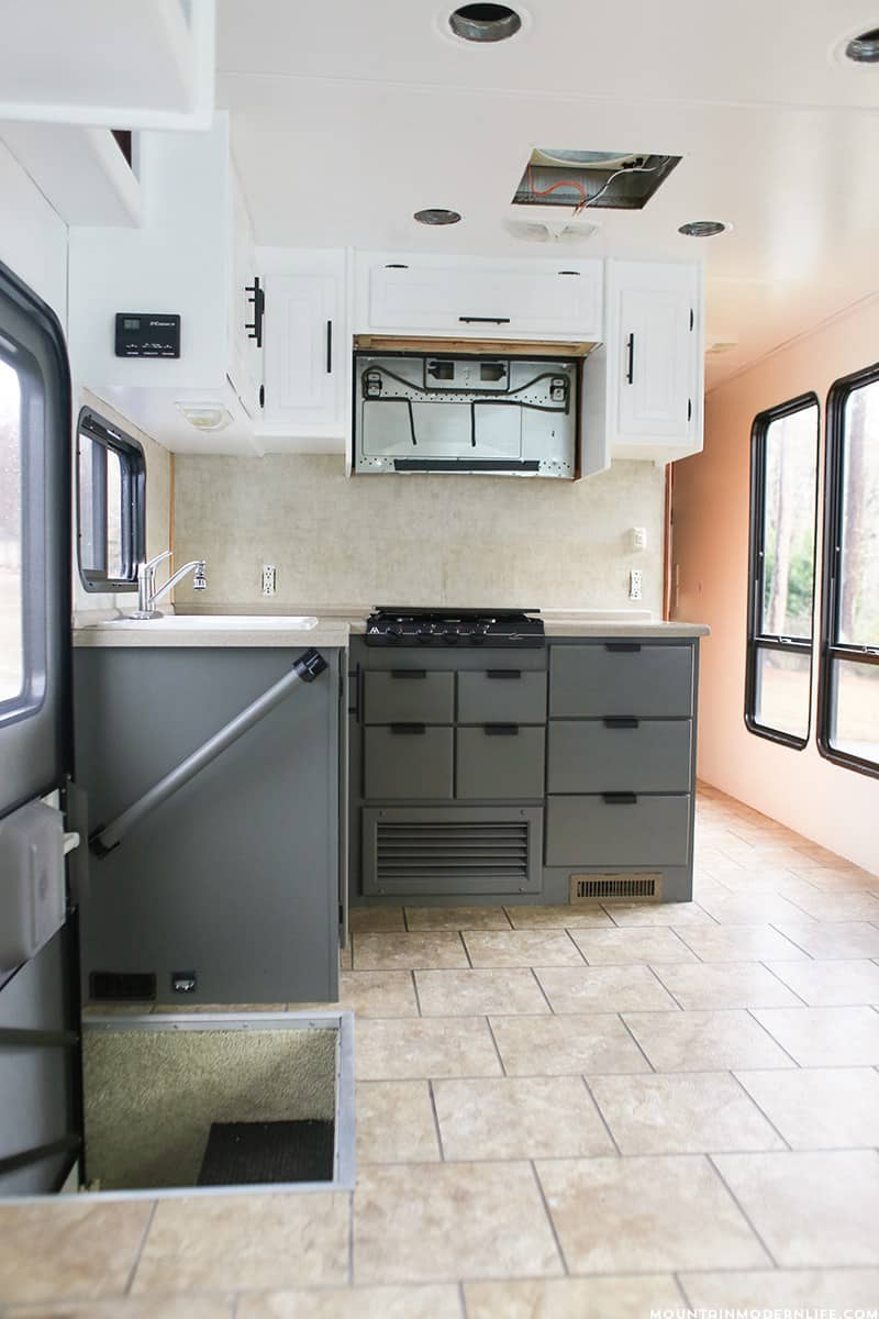 Planning to paint your tiny kitchen and considering the two-tone look? Come see our painted RV kitchen cabinets, and the mistakes I made along the way. MountainModernLife.com