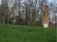 The remains of the Frenchman's Settlement after an arsonist's fire, along with a picnic shelter.