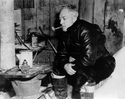 Rear Admiral Richard Byrd revisits his old hut at the site of Little America II. He is smoking 12-year old tobacco in a 12-year old corncob pipe left at the camp in 1935. This photo was taken in 1947 during the US Navy's Operation Highjump expedition by US Navy, National Science Foundation