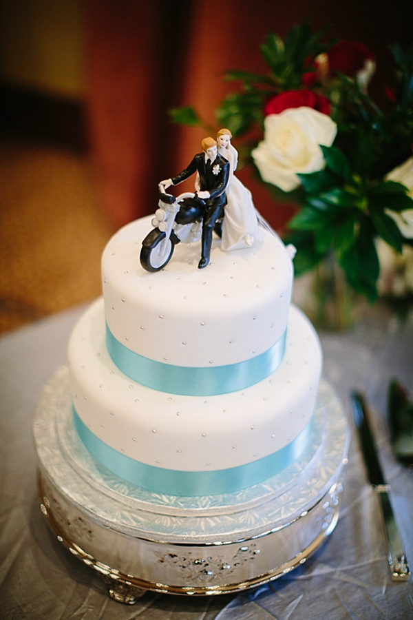 wedding cake with turquoise ribbon and motorcycle cake topper