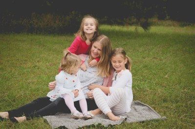 Mom giggling with three daughters at photo shoot via Ashley Stevens at Mountains Unmoved