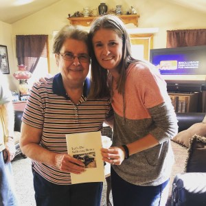 Ashley Stevens at Mountains Unmoved holding her book - Let's Do Suffering Better - with grandma