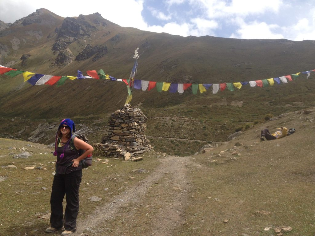 A hiker posing in front of prayer flags in Nepal.